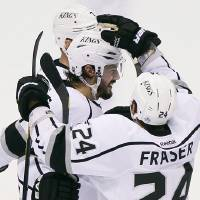 Photo -   Los Angeles Kings defenseman Drew Doughty, center, is congratulated by Colin Fraser (24) and Rob Scuderi after scoring a goal during the second period of Game 5 of the NHL hockey Stanley Cup Western Conference finals against the Phoenix Coyotes, Tuesday, May 22, 2012, in Glendale, Ariz. (AP Photo/Matt York)
