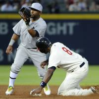 Photo - Atlanta Braves' Justin Upton (8) is safe at second base as Oakland Athletics' Alberto Callaspo fields the late throw on a wild pitch during the fourth inning of a baseball game Saturday, Aug. 16, 2014, in Atlanta. (AP Photo/David Tulis)