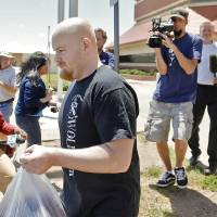 Photo - Attorney Irven Box walks with Justin Adams as he is released July 25 from the Oklahoma County jail in Oklahoma City on a  $100,000 bond.  Photo by Chris Landsberger, The Oklahoman  CHRIS LANDSBERGER