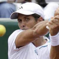 Photo - Fernando Verdasco of Spain returns a shot to Santiago Giraldo of Colombia in a semifinal match at the U.S. Men's Clay Court Championship, Saturday, April 12, 2014, in Houston. Verdasco won 6-4, 7-5. (AP Photo/Pat Sullivan)