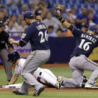 Photo - Milwaukee Brewers third baseman Aramis Ramirez (16) tags out Tampa Bay Rays' Logan Forsythe at third base after he was caught trying to stretch a double into a triple during the fifth inning of an interleague baseball game Monday, July 28, 2014, in St. Petersburg, Fla. Looking on is Brewers pitcher Kyle Lohse (26) and umpire John Tumpane. (AP Photo/Chris O'Meara)
