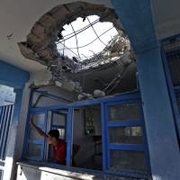 """Photo - A displaced Palestinian child waves to a friend from inside a damaged classroom at the Abu Hussein U.N. school, in Jebaliya refugee camp, northern Gaza Strip, Wednesday, July 30, 2014.T he U.N. condemned Wednesday's attack on the school, with Secretary-General Ban Ki Moon calling it """"outrageous"""" and """"unjustifiable."""" Israel said no U.N. facility had been intentionally targeted, but troops had responded to Hamas mortar fire nearby.  (AP Photo/Lefteris Pitarakis)"""