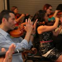 "Photo -  Guests can learn the basics of playing the violin in a relaxed setting at the Oklahoma City Philharmonic's ""Violins & Vino."" Photo provided"