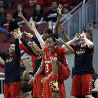 Photo - Maryland guard Shatori Walker-Kimbrough (32) and the bench reacts after a 3-point basket during the first half of a regional semifinal game against Tennessee at the NCAA college basketball tournament on Sunday, March 30, 2014, in Louisville, Ky. (AP Photo/John Bazemore)