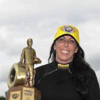 Photo - In this photo provided by NHRA, Alexis DeJoria holds her trophy Monday Sept. 1, 2014, in Brownsurg, Ind., after racing to the Funny Car victory at the 60th annual Chevrolet Performance U.S. Nationals at Lucas Oil Raceway.  DeJoria, is the fourth female to win the event in NHRA history.  (AP Photo/Jerry Foss)