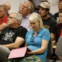 Photo - Area residents and registered speakers watch proceedings on a television screen from one of the three overflow rooms as others wait their turn to address the city council during a public hearing, Tuesday, July 15, 2014, in Denton, Texas. The North Texas city could become the first in the state to ban hydraulic fracturing if city leaders approve a citizen-led petition to outlaw the drilling method. (AP Photo/Tony Gutierrez)