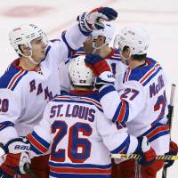 Photo - New York Rangers' Martin St. Louis (26)celebrates his goal against the Ottawa Senators with teammates Chris Krieder (20) Ryan McDouagh (27) during second period NHL hockey action in Ottawa, Ontario, Tuesday March 18, 2014.(AP Photo/The Canadian Press, Fred Chartrand)