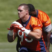 Photo -   Denver Broncos rookie defensive tackle Derek Wolfe stretches during NFL football practice at the team's training facility in Englewood, Colo., on Wednesday, June 13, 2012. (AP Photo/Ed Andrieski)