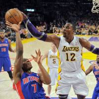 Photo -   Los Angeles Lakers center Dwight Howard, right, blocks the shot of Detroit Pistons guard Brandon Knight during the first half of their NBA basketball game, Sunday, Nov. 4, 2012, in Los Angeles. (AP Photo/Mark J. Terrill)