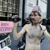 Photo - Chuck Newell records a demonstration against a nudity ban outside a Federal building Thursday, Jan. 17, 2013 in San Francisco. Activists are asking a federal judge to block a city ordinance banning public nudity. The ban is scheduled to go into effect Feb. 1. The local law has become a divisive political issue in a town that prides itself on its inhibitions. The demonstration took place before a court hearing on the ordinance. (AP Photo/Eric Risberg)