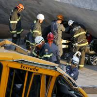 Photo - Fire department personnel work to retrieve a car from underneath a collapsed bridge in Belo Horizonte, Brazil, Thursday, July 3, 2014. The overpass under construction collapsed Thursday in the Brazilian World Cup host city. The incident took place on a main avenue, the expansion of which was part of the World Cup infrastructure plan but, like most urban mobility projects related to the Cup, was not finished on time for the event. (AP Photo/Victor R. Caivano)