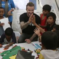 Photo - Former England soccer team captain David Beckham interacts with typhoon survivors during his visit to Typhoon Haiyan-hit Tacloban city, central Philippines, Thursday, Feb. 13, 2014. Beckham visited the storm-devastated Philippine city as part of UNICEF's relief efforts. (AP Photo/Bullit Marquez)