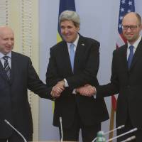 Photo - U.S. Secretary of State John Kerry, center,  greets Ukrainian Prime Minister Arseniy Yatsenyuk, right, and parliament speaker Oleksandr Turchynov prior their meting in Kiev, Ukraine, Tuesday, March, 4, 2014.  In a somber show of U.S. support for Ukraine's new leadership, Secretary of State John Kerry walked the streets Tuesday where nearly 100 anti-government protesters were gunned down by police last month, and promised beseeching crowds that American aid is on the way.  The Obama administration announced a $1 billion energy subsidy package in Washington as Kerry was arriving in Kiev.( (AP Photo/Andrew Kravchenko, pool)
