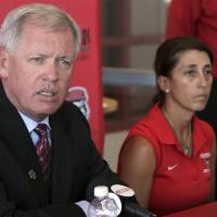 Photo - University of New Mexico athletic director Paul Krebs, left, discusses a hazing incident involving the women's soccer team as head coach Kit Vela sits beside him during a news conference in Albuquerque, N.M., on Wednesday, Aug. 20, 2014. Krebs said the hazing involved alcohol and the team is now undergoing a hazing education class and will have to perform community service. Officials said other sanctions are possible pending the completion of an investigation. (AP Photo/Susan Montoya Bryan)