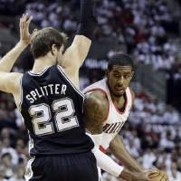 Photo - Portland Trail Blazers forward LaMarcus Aldridge, right, looks for room to maneuver against San Antonio Spurs forward Tiago Splitter, from Brazil, during the first half of an NBA basketball game in Portland, Ore., Saturday, Nov. 2, 2013. (AP Photo/Don Ryan)