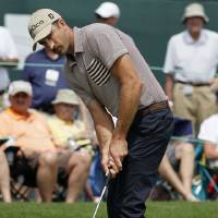Photo -   Geoff Ogilvy, of Australia, putts on the 18th green during the third round of the Wells Fargo Championship golf tournament at Quail Hollow Club in Charlotte, N.C., Saturday, May 5, 2012. (AP Photo/Gerry Broome)