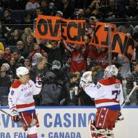 Photo - Washington Capitals'  Alex Ovechkin (8) of Russia, celebrates his second goal with Braden Holtby (70) and Washington fans during the first period of an NHL hockey game against the Buffalo Sabres in Buffalo, N.Y., Tuesday, Jan. 28, 2014. (AP Photo/Gary Wiepert)