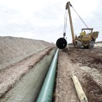 Photo - CONSTRUCTION: Workers use heavy machinery to install sections of the Keystone Pipeline south of Cushing, OK, Tuesday, January 15, 2013,  By Paul Hellstern, The Oklahoman