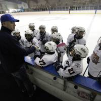 Photo - Coach Peter Robertson talks to his players in a game between the Oklahoma City Oil Kings and the New Mexico Warriors during the Oktoberfest 2012 youth hockey tournament at Arctic Edge Arena in Oklahoma City.  Photo by Garett Fisbeck, The Oklahoman  Garett Fisbeck