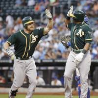 Photo - Oakland Athletics Brandon Moss, left, greets Athletics Yoenis Cespedes at the plate after hitting a first-inning, two-run home run off New York Mets starting pitcher Zack Wheeler in an interleague baseball game in New York, Wednesday, June 25, 2014. (AP Photo/Kathy Willens)