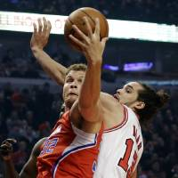Photo - Los Angeles Clippers forward Blake Griffin, left, grabs a rebound over Chicago Bulls center Joakim Noah during the first half of an NBA basketball game, Tuesday, Dec. 11, 2012, in Chicago. (AP Photo/Charles Rex Arbogast)