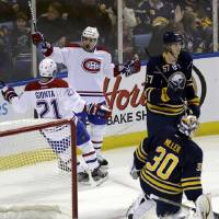 Photo - Montreal Canadiens' Tomas Plekanec (14), of the Czech Republic, celebrates his goal with Brian Gionta (21) on Buffalo Sabres' Ryan Miller (30), as Sabres' Tyler Myers (57) looks away during the first period of an NHL hockey game in Buffalo, N.Y., Thursday, Feb. 7, 2013. (AP Photo/David Duprey)