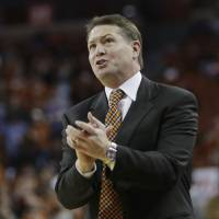 Photo - Oklahoma State coach Travis Ford talks to his players during the first half on an NCAA college basketball game against Texas, Tuesday, Feb. 11, 2014, in Austin, Texas. Texas won 87-68. (AP Photo/Eric Gay)