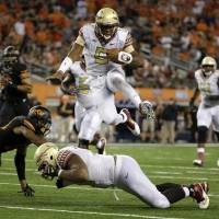 Photo - Florida State quarterback Jameis Winston (5) leaps over guard Josue Matias as Oklahoma State safety Jordan Sterns, left, is unable to stop Winston from reaching the end zone for a touchdown in the second half of an NCAA college football game, Saturday, Aug. 30, 2014, in Arlington, Texas. (AP Photo/Tony Gutierrez)