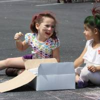 Photo - Briana Villanueva, 4, left, and Ivy Collier, 5, make chalk drawings at the  block party in Norman sponsored by the Center for Children and Families. PHOTO BY LYNETTE LOBBAN, FOR THE OKLAHOMAN