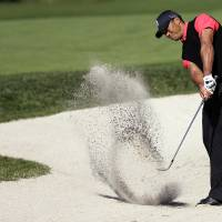 Photo - Tiger Woods hits out of a bunker on the 10th hole during the fourth round of the Farmers Insurance Open golf tournament at the Torrey Pines Golf Course, Monday, Jan. 28, 2013, in San Diego. (AP Photo/Gregory Bull)