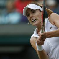 Photo - Alize Cornet of France returns a point to Serena Williams of U.S. during their women's singles match at the All England Lawn Tennis Championships in Wimbledon, London, Saturday, June 28, 2014. (AP Photo/Sang Tan)