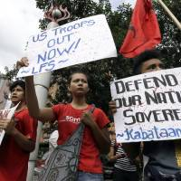 Photo - Protesters display placards during a rally at the U.S. Embassy in Manila to protest the recent incident in the Philippines wherein a U.S. Navy minesweeper, the USS Guardian, ran aground off Tubbataha Reef, a World Heritage Site in the Sulu Sea, 640 kilometers (400 miles) southwest of Manila, Philippines Saturday Jan. 19, 2013. The protesters are demanding the abrogation of the Visiting Forces Agreement which allows U.S. troops' presence in the country. (AP Photo/Bullit Marquez)