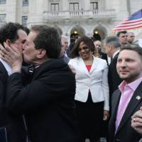 Photo - Rhode Island House Speaker Gordon Fox, left, is kissed by R.I. Rep. Frank Ferri, D-Warwick, after a gay marriage bill was signed into law outside the State House in Providence, R.I., Thursday, May 2, 2013. (AP Photo/Charles Krupa)