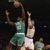 Photo - Boston Celtics forward Brandon Bass (30) grabs the ball in front of New York Knicks forward Kenyon Martin (3) during the first half of Game 1 in the first round of the NBA basketball playoffs at Madison Square Garden in New York, Saturday, April 20, 2013.  (AP Photo/Kathy Willens)