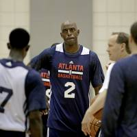Photo - Atlanta Hawks' Damien Wilkins, center, listens  to head coach Mike Budenholzer, second from right, during NBA basketball training camp, Tuesday, Oct. 1, 2013, in Athens, Ga. (AP Photo/David Goldman)