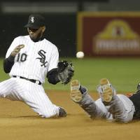 Photo - Miami Marlins' Adeiny Hechavarria, right, steals second as Chicago White Sox shortstop Alexei Ramirez cannot make a catch during the eighth inning of a baseball game on Friday, May 24, 2013, in Chicago. (AP Photo/Nam Y. Huh)