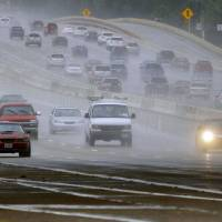 Photo - Rains pounds the Central Expressway Thursday, July 17, 2014 near the President George Bush Turnpike in Collin County, Texas. Heavy rains and localized flooding were expected as a strong storm system moved in to the region Thursday. (AP Photo/The Dallas Morning News, G.J. McCarthy)