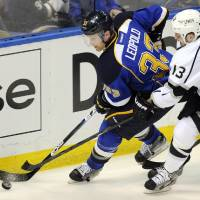 Photo - St. Louis Blues' Jordan Leopold (33) and Los Angeles Kings' Kyle Clifford (13) reach for the puck during the second period of Game 1 of their first-round NHL hockey Stanley Cup playoff series, Tuesday, April 30, 2013, in St. Louis. (AP Photo/Bill Boyce)