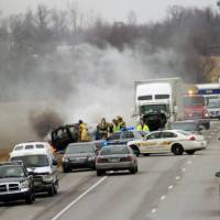 Photo - Emergency personnel work at the scene of a multi-vehicle wreck on Interstate 65 near the 82 mile marker, Saturday, March 2, 2013 north of Sonora, Ky. Kentucky State Police say six people are dead in two crashes that happened near the same location in central Kentucky on Interstate 65. (AP Photo/The News Enterprise, Neal Cardin)