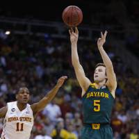 Photo - Baylor guard Brady Heslip (5) shoots a 3-point basket as Iowa State guard Monte Morris (11) defends during the first half of an NCAA college basketball game in the final of the Big 12 Conference men's tournament in Kansas City, Mo., Saturday, March 15, 2014. (AP Photo/Orlin Wagner)