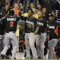 Photo -   Miami Marlins' Hanley Ramirez, 2, is greeted at the dugout by teammates Jose Reyes, third from right, and Emilio Bonifacio, second from right, after scoring the winning run off a hit by teammate Omar Infante against the San Diego Padres in the twelfth inning during their baseball game Friday, May 4, 2012, in San Diego. (AP Photo/Gregory Bull)
