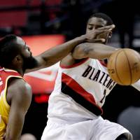Photo - Houston Rockets guard James Harden, left, plays tight defense on Portland Trail Blazers guard Wesley Matthews during the first quarter of an NBA basketball game in Portland, Ore., Friday, April 5, 2013. (AP Photo/Don Ryan)
