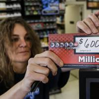 Photo - Sheila Sutton updates the Powerball prize money sign at the Super C convenience store in Lincoln, Neb., Friday, May 17, 2013. Powerball officials say the jackpot has climbed to an estimated $600 million, making it the largest prize in the game's history and the world's second largest lottery prize.  Sutton sold a million dollar powerball ticket on Tuesday. (AP Photo/Nati Harnik)