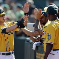 Photo -   Oakland Athletics' Josh Reddick, left, receives high-fives after scoring on a single from Seth Smith during the fourth inning of a baseball game against the Texas Rangers on Wednesday, Oct. 3, 2012, in Oakland, Calif. (AP Photo/Marcio Jose Sanchez)