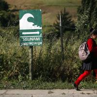 Photo - In this photo taken Nov. 29, 2012, a student walks past a sign indicating an evacuation route in the event of a tsunami, in Navidad, Chile. The road to the town of Navidad (Christmas in Spanish) is lined by a forest of eucalyptus trees and wildflowers that grow around painted tsunami warning signs that urge residents to build their homes high or dash for higher ground in case of a quake. (AP Photo/Luis Hidalgo)