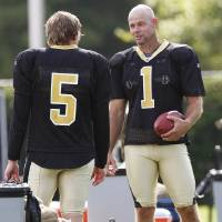 Photo - New Orleans Saints' John Carney (1) talks with fellow placekicker Garrett Hartley (5) at the morning practice session at the club's NFL football training facility in Metairie, Sunday, Aug. 16, 2009. It was Carney's first practice since signing a contract with the Saints. (AP Photo/Bill Haber) ORG XMIT: LAWH101