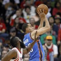 Photo - Oklahoma City Thunder guard Kevin Martin (23) shoots next to Houston Rockets guard James Harden during the second half of an NBA basketball game, Saturday, Dec. 29, 2012, in Houston. The Thunder won 124-94. (AP Photo/Bob Levey) ORG XMIT: TXBL112