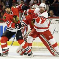 Photo - Detroit Red Wings' Daniel Cleary, right, and Chicago Blackhawks' Michal Rozsival battle as they wait for the puck during the first period of Game 1 of an NHL hockey playoffs Western Conference semifinal in Chicago, Wednesday, May 15, 2013. (AP Photo/Nam Y. Huh)