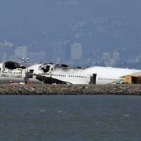 Photo - The wreckage of Asiana Airlines Flight 214 that crashed upon landing Saturday at San Francisco International Airport sits on the tarmac Monday, July 8, 2013 in San Francisco. Investigators said the Boeing 777 was traveling