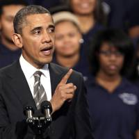 Photo - President Barack Obama speaks about strengthening the economy for the middle class and the nations struggle with gun violence at an appearance at Hyde Park Academy, Friday, Feb. 15, 2013, in Chicago.  (AP Photo/M. Spencer Green)